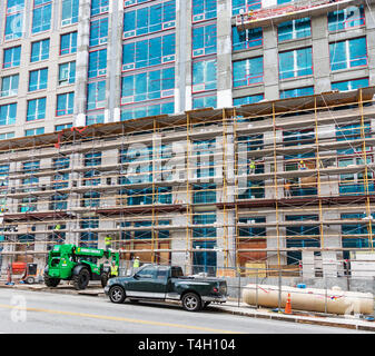 ASHEVILLE, NC, USA-4/11/19:  Workers on scaffolding on the outside of the Arras Building, with a boom lift parked on the street, on Broadway Avenue, n - Stock Image