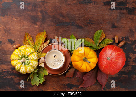 Autumn still life with pumpkins, coffee and colorful leaves over wooden background. Top view with space for your text - Stock Image