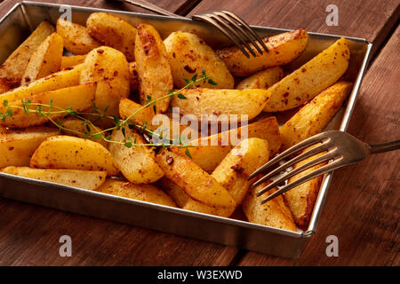 Potato wedges, oven roasted, with thyme, a close-up in a baking tray, with two forks - Stock Image