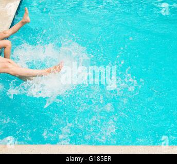 Legs splashing water in swimming pool - Stock Image