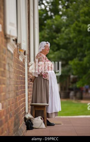 Woman standing on doorstep at Colonial Williamsburg, Virginia, USA - Stock Image