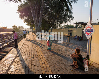 A female western tourist waiting for a train at Hosapete JN railway station near Hampi in India - Stock Image