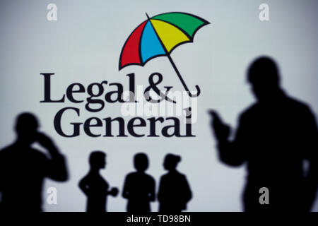 The Legal and General logo is seen on an LED screen in the background while a silhouetted person uses a smartphone (Editorial use only). - Stock Image