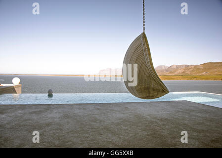Swing chair hanging at poolside in resort - Stock Image