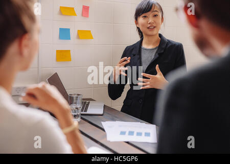 Businesswoman standing by a wall with sticky notes leading a business presentation. Female executive putting her - Stock Image