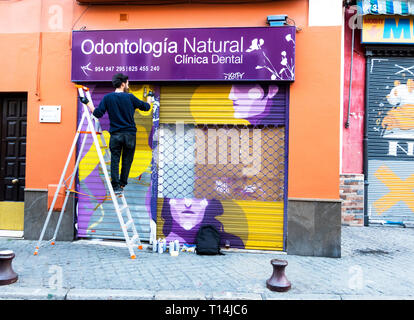A street artist painting a picture on the shutters of a dental clinic in Seville - Stock Image