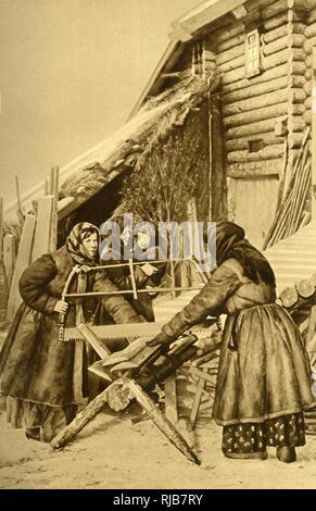 Peasant women sawing wood in winter, wearing warm sheepskin coats, Republic of Estonia. - Stock Image