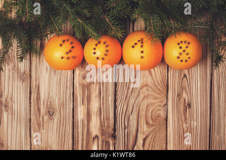 Christmas decorations with oranges and numbers of cloves on a wooden background - Stock Image