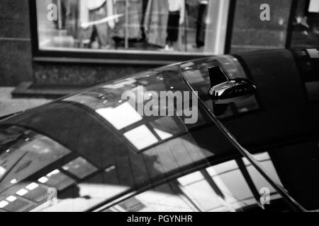 Reflection of the lines and shapes of the shop window on the glass and roof of the car. Black and white stylization - Stock Image