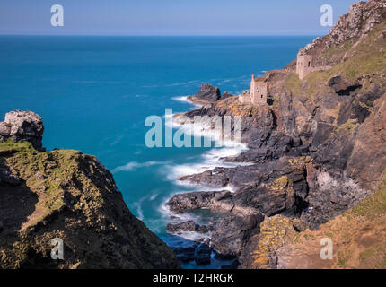 Disused tin mine buildings on dramatic cliff edges of north Atlantic coast, Botallack, Cornwall, England, UK - Stock Image