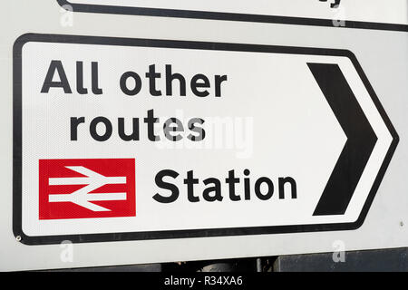 A Class 2 (high intensity) retroflective road sign in England with directions to a train station and all other routes - Stock Image