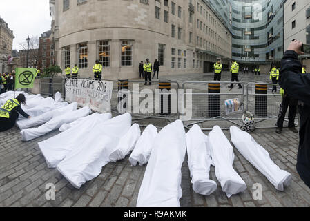 London, UK. 21st December 2018. Climate campaigners from Extinction Rebellion bring 'bodies' - mannequins wrapped in white cloth to the BBC representing the bodies of a Greek village killed by fire because of global warming. The protest at the BBC called it to stop ignoring the climate emergency & mass extinctions taking place and promoting destructive high-carbon living through programmes such as Top Gear and those on fashion, travel, makeovers etc. It was organised by the Climate Media Coalition (CMC) and its director Donnachadh McCarth . Peter Marshall/Alamy Live News - Stock Image