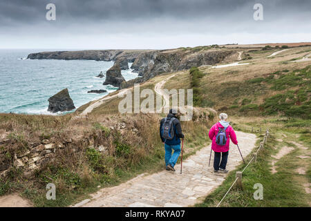 Two mature walkers walking down the South West Coast Path to Bedruthan Steps in Cornwall. - Stock Image