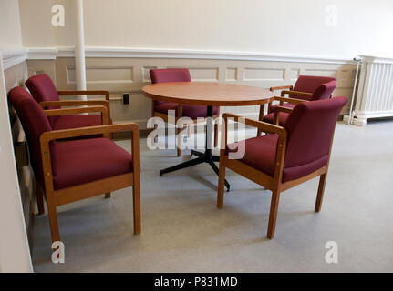 Five empty chairs around a table in a school or office workspace - Stock Image