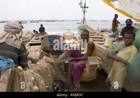 Fishermen carrying out routine maintenance on their fishing gear on the town beach at Winneba Ghana - Stock Image