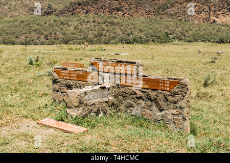 A stone wall with signed directions, Hells Gate National Park, Kenya - Stock Image
