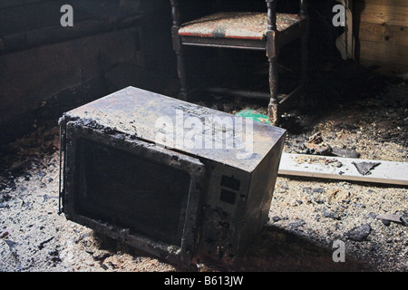 Microwave oven in burned house - Stock Image