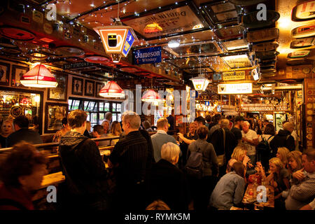 People drinking inside the Duke of York pub. - Stock Image