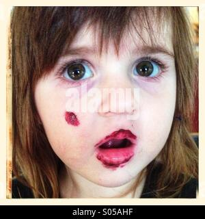 Little girl with paint on her face - Stock Image