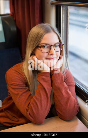 Portrait of smiling woman in train - Stock Image