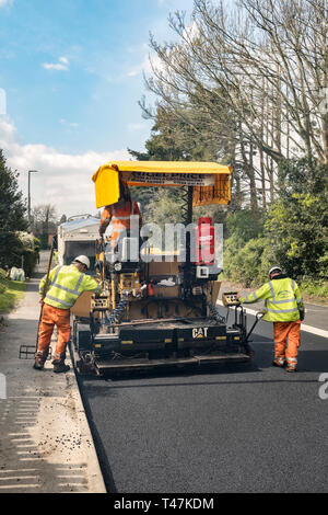 Presteigne, Powys, Wales, UK. An asphalt paver or paving machine laying fresh tarmac on a road in the town - Stock Image