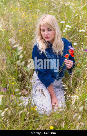 Romantic young blonde woman holding red poppy flowers in a field with high grasses - Stock Image