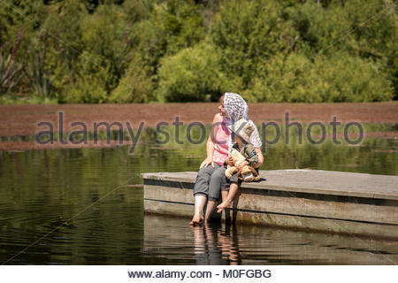 Mother and son  sitting on  wooden pier - Stock Image