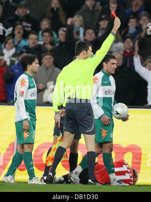 Referee Wolfgang Stark (C) shows Hugo Almeida (not in the picture) of Bremen the red card during the Bundesliga - Stock Image
