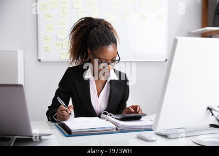 Close-up Of A Businesswoman's Hand Calculating Invoice In Office - Stock Image