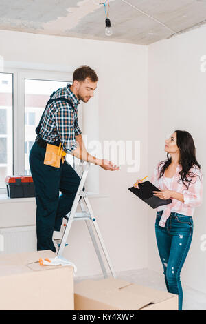 cheerful woman holding clipboard and looking at handyman standing on ladder - Stock Image