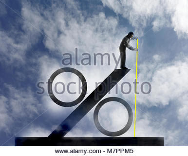 Businessman measuring size of large percentage sign - Stock Image