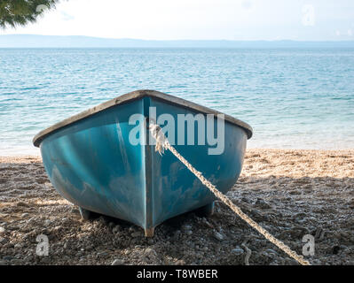 Blue boat with rope on the beach close to the blue sea background - Stock Image