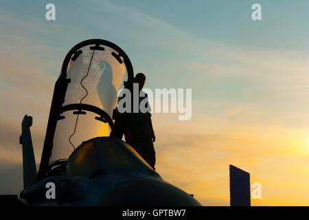 Dawn early morning sunrise scenic on aircraft nose silhouette mechanic ground crew  opened canopy cockpit misty - Stock Image
