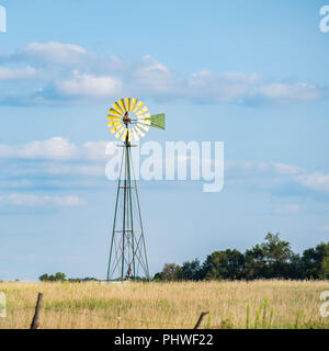 A farm windmill used for livestock water source against blue sky in the Oklahoma farmland, countryside. USA. - Stock Image