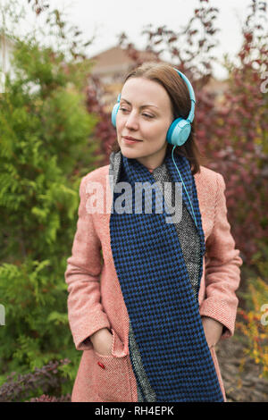 Woman in scarf and coat listening to music with headphones - Stock Image