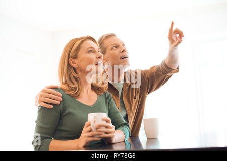 man pointing with finger while hugging wife with coffee cup in hands - Stock Image