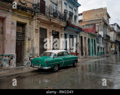 Old American car glistens in the rain in the wet back streets after a Caribbean storm in Havana, Cuba - Stock Image