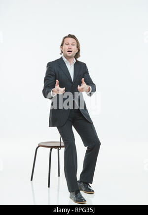 The handsome men in black suits differently pose on a white background, good luck - Stock Image