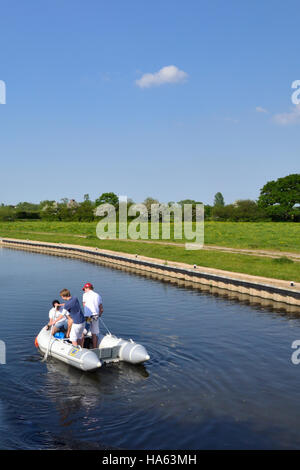 Three male teenagers having fun in a rubber dingy on the Trent & Mersey Canal near Alrewas. - Stock Image