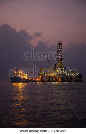 Boat by offshore oil platform at sunset - Stock Image
