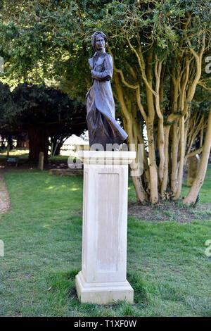Bronze statue of Jane Austen (b.16 December 1775-d.18 July 1817) by Adam Roud in St Nicholas Church Churchyard, Chawton, near Alton, Hampshire, UK. - Stock Image