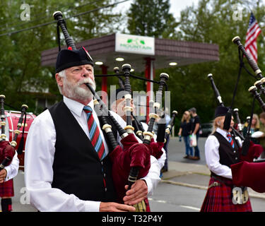 A bagpiper marching and playing in the 4th of July parade in Speculator, NY USA - Stock Image
