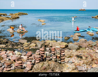 Dunbar, East Lothian, Scotland, UK. 21st Apr 2019. UK Weather: People enjoy the very sunny hot Easter day weather at Eye Cave cove. A family enjoys paddle boarding - Stock Image