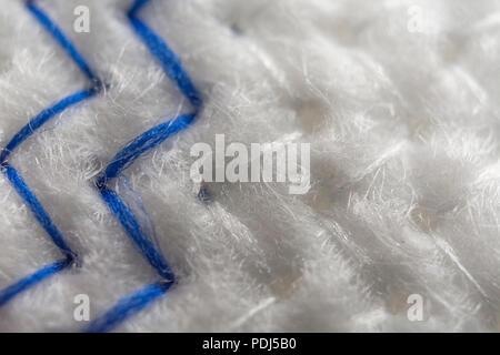 Close-up macro shot of zig-zag herringbone stitches of kitchen dishcloth. - Stock Image