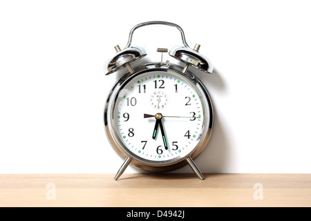 Chrome alarm clock with bells on, set just before 6-30 - Stock Image