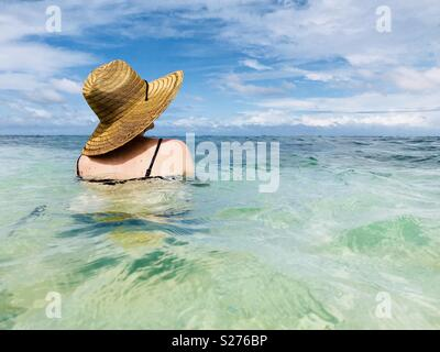 A women with a hat on sitting in the water. Tavarua Island, Fiji. - Stock Image