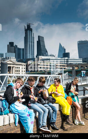 A group of Scouts eating food on the South Bank in London. - Stock Image