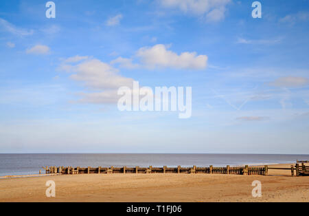 A view of a wooden breakwater with access break to aid coast protection on the North Norfolk coast at Bacton-on-Sea, Norfolk, England, United Kingdom. - Stock Image