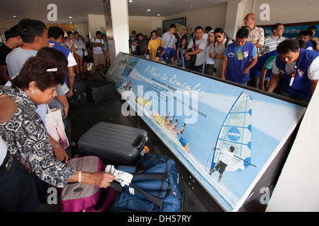 Travelers collect their luggage from the baggage carousel at Tagbilaran Aiport in Bohol, Philippines. - Stock Image