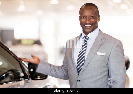 friendly African car dealer presenting new vehicle in showroom - Stock Image